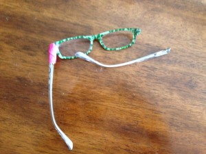 Glasses horribly bent, one arm off and one fixed with bright pink duct tape
